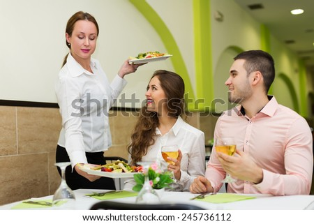Positive waitress brings plate with prepared food to visitors table - stock photo