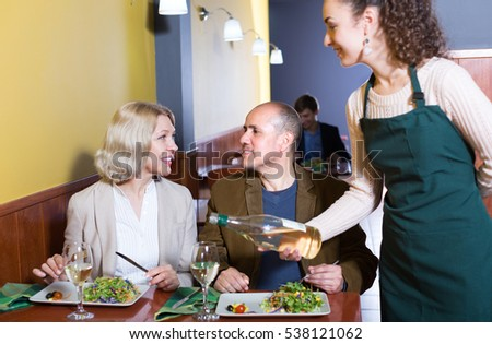 Positive waitress serving mature guests at the table in restaurant