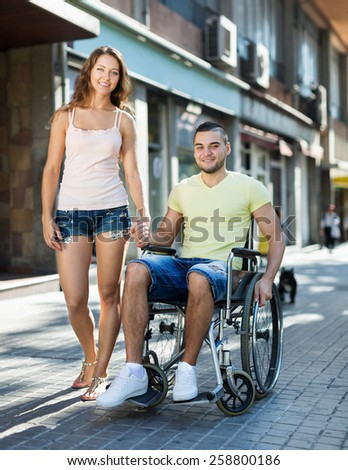 Positive woman and her disabled husband in wheelchair outdoor  - stock photo