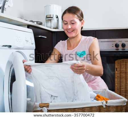 Positive  woman doing laundry at home and smiling