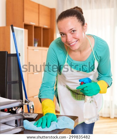 Positive woman professional cleaner cleaning office room   - stock photo