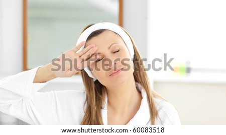 Positive woman putting cream on her face wearing a headband in the bathroom at home