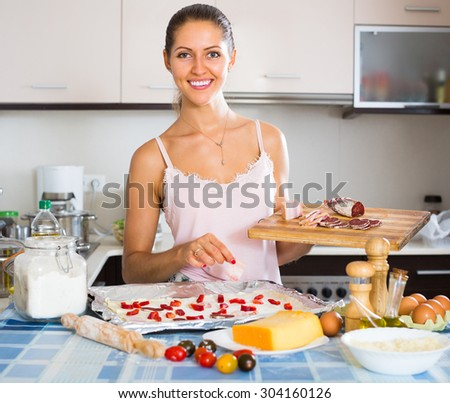 Positive woman putting vegetables and ham on pizza