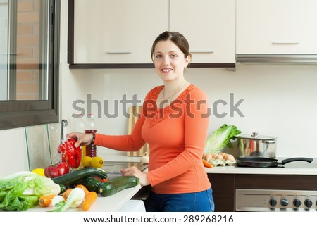 positive woman washing pepper and other vegetables in sink at home