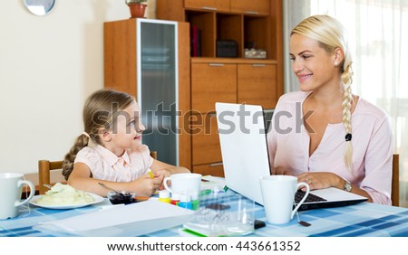 Positive woman with daughter working from home using laptop