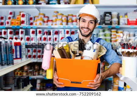 Positive  workman holding basket with picked tools in paint store
