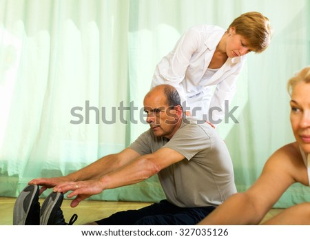 Positive yoga instructor showing new asana elderly couple  - stock photo