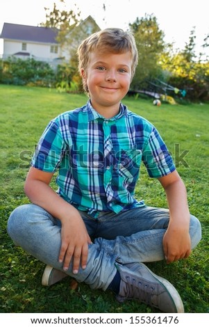 Positive young boy sitting on a meadow