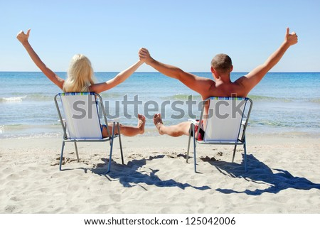 Positive young couple sitting on the beach chair on the sea beach up their hands and looking at see surface - stock photo