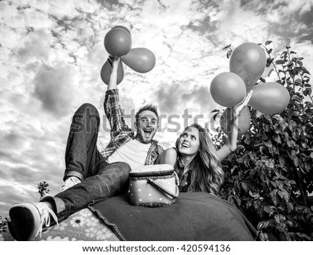 Positive young couple spending time outdoors. Black-white photo.