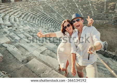 Positive young couple take self photo in Side amphitheatre - stock photo