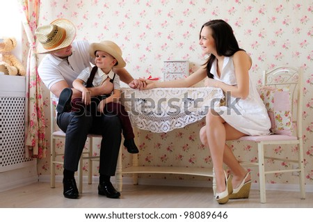 positive young family sitting around the dinner table. light room - stock photo