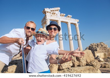Positive young family take a selfie photo near antique Temple of Apollo,Side,Turkey - stock photo