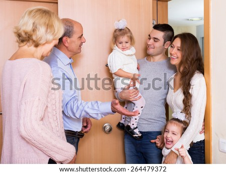 Positive young family with two daughters visiting grand parents  - stock photo