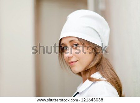 Positive young nurse in hospital interior