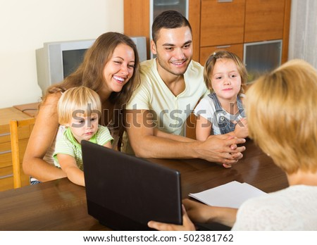 Positive young parents and two daughters sitting in front of social worker