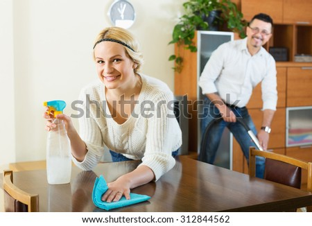 Positive young spouses dusting and hoovering at domestic interior - stock photo