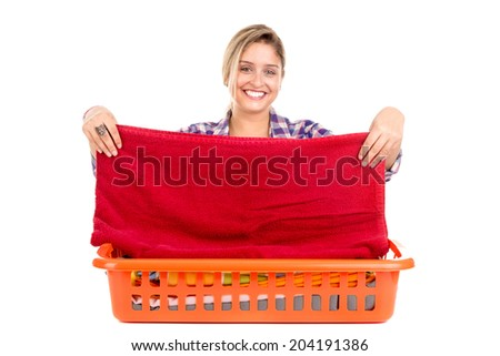 Positive young woman doing the laundry at home - stock photo