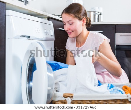Positive young woman 25-30 years old doing laundry at home   - stock photo