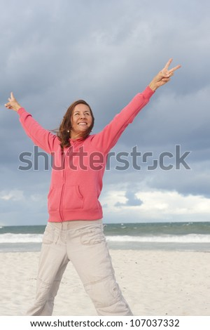 Positiver and optimistic mature woman, standing happy with a smile at the beach, arms up, isolated with ocean and storm clouds as background and copy space. - stock photo