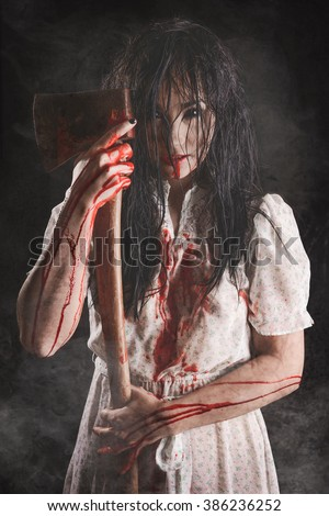 Possessed girl with Bloody axe - stock photo