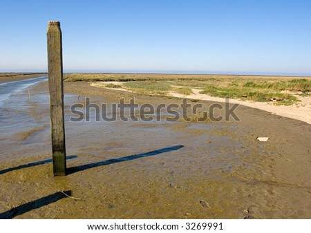 Post at the beach at low-tide - stock photo