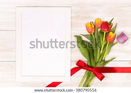 Post blog social media 8 march. View from above with copy space. Banner template layout mockup for woman day. White wooden table, top view on workplace. Lilac tulips at the Desk with frame. - stock photo