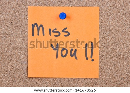 Post it note orange with miss you message on cork - stock photo