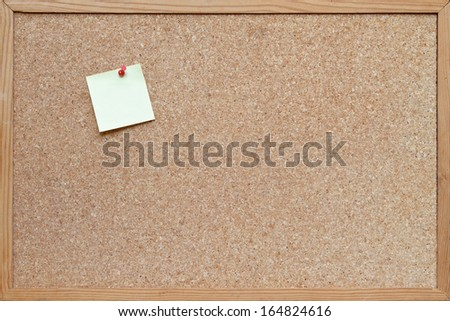 post it note pinned to a blank cork board / bulletin board with a wooden frame - stock photo