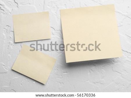 Post-it notes on white textured wall - stock photo