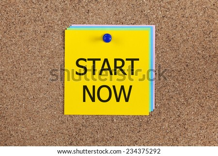"""Post-it notes with words """"Start now"""" on cork board (bulletin board). - stock photo"""