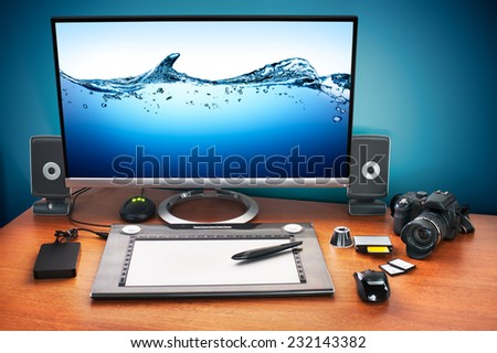 Post production desk with digital camera, memory cards, graphic tablet, and monitor to advertise youself and your work. - stock photo