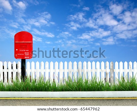 postbox on road side with white fence and blue sky - stock photo
