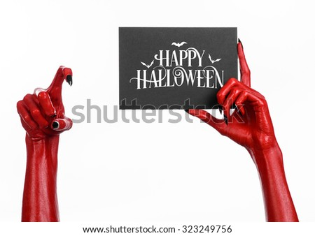 Postcard and Happy Halloween theme: red devil hand with black nails holding a paper card with the words Happy Halloween on a white isolated background in studio - stock photo