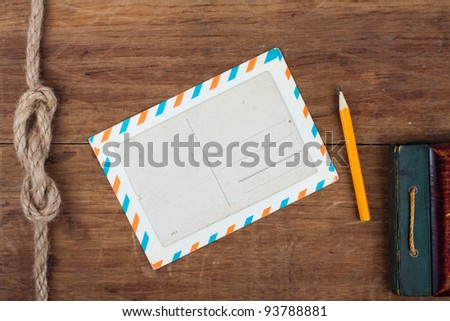Postcard, envelope, pencil on wooden background - stock photo