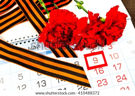 Postcard for 9 May Victory Day in Great Patriotic War in Russia- St George ribbon and red carnations over the calendar with framed 9 May date. 9 May concept.   - stock photo