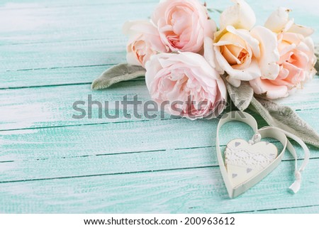 Postcard with fresh flowers and decorative heart on wooden background. Country chic. Selective focus, horizontal. - stock photo