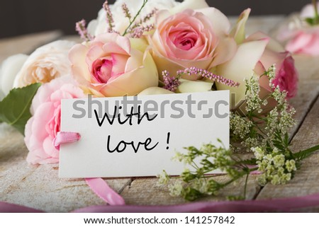 Postcard with fresh flowers and tag with words with love - stock photo