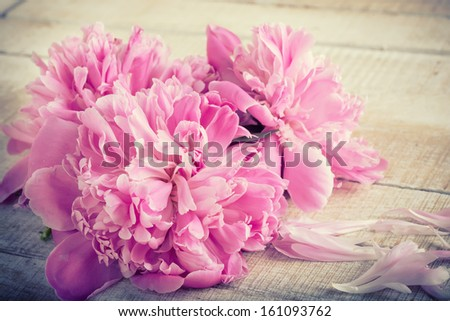 Postcard with fresh pink peonies on wooden background. Selective focus. - stock photo
