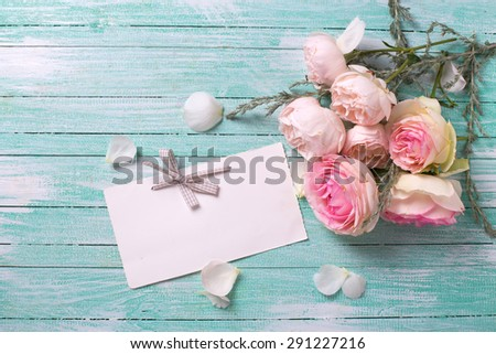 Postcard with fresh roses flowers and empty tag for your text on turquoise painted wooden background. Selective focus. - stock photo