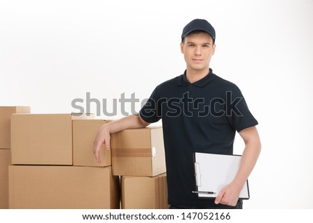 Postman at work. Cheerful young deliveryman holding a clipboard with documents while leaning at the box stack - stock photo