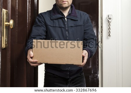Postman delivers parcel - stock photo