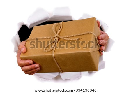 Postman hands delivering or giving parcel through torn white paper background - stock photo