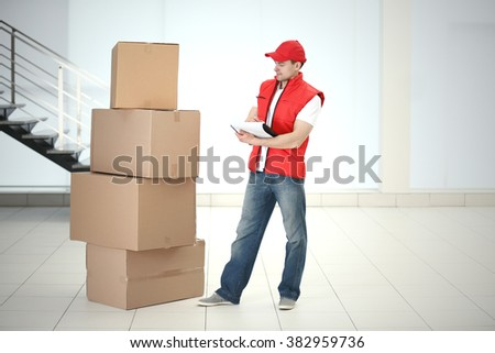Postman in red jacket near pile of carton boxes in the room - stock photo