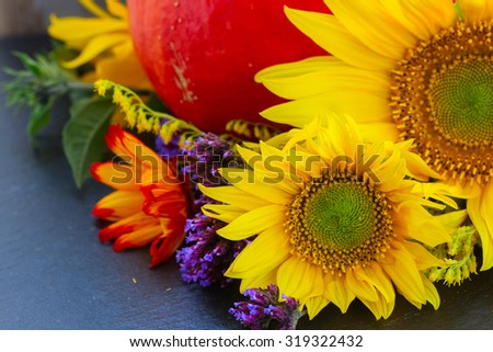 posy of fresh mixed autumn flowers with raw pumpkin - stock photo