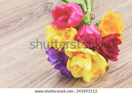 posy  of pink tulips,  yellow daffodils and freesea flowers on wooden table,  instagram retro filter - stock photo