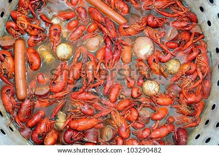 Pot And Basket Of Hot Boiled Louisiana Crawfish With Potatoes,Corn, Garlic, Mushrooms  And Sausage - stock photo