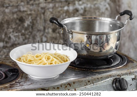pot and dish on old gas stove - stock photo