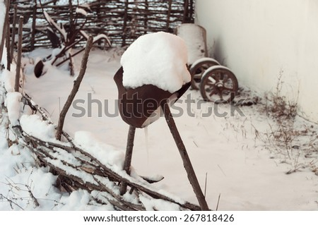 Pot covered with snow on a fence in winter village - stock photo