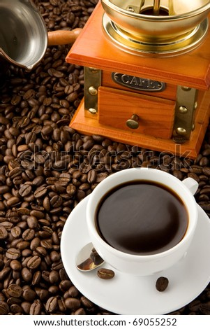 pot, grinder and cup of on coffee beans - stock photo
